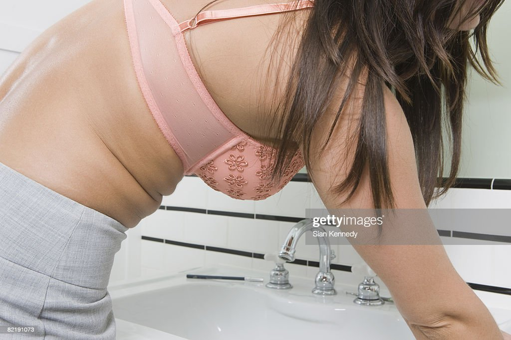 Woman in the bathroom getting dressed : Stock Photo