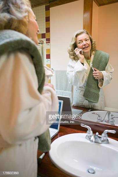 Woman in the bathroom talking on cellphone