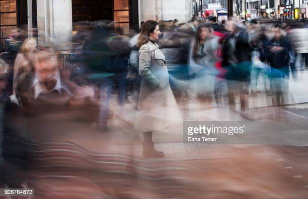 woman in the big city surrounded by blurry pedestrians - 長時間露光 ストックフォトと画像