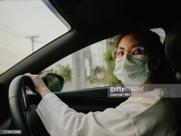 woman in the car with protective facial mask.health protection. - driving mask stock pictures, royalty-free photos & images