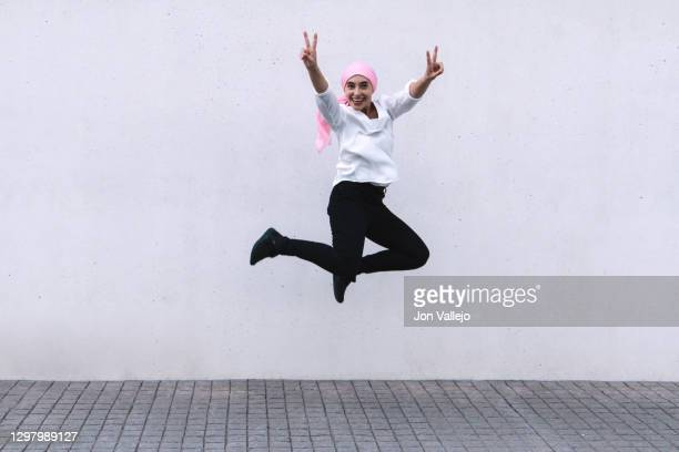woman in the centre of the image smiling and jumping up and down with her legs shrunk and making the victory sign with both hands. she is wearing a pink scarf in reference to cancer, black pants and a white blouse. - best bosom stock pictures, royalty-free photos & images