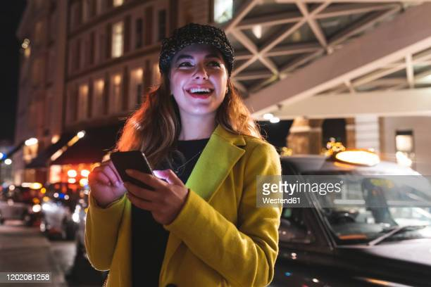 woman in the city at night typing on her smartphone and smiling - hotel stock pictures, royalty-free photos & images