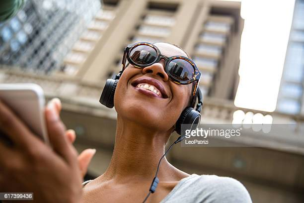 Woman in the city listening to music