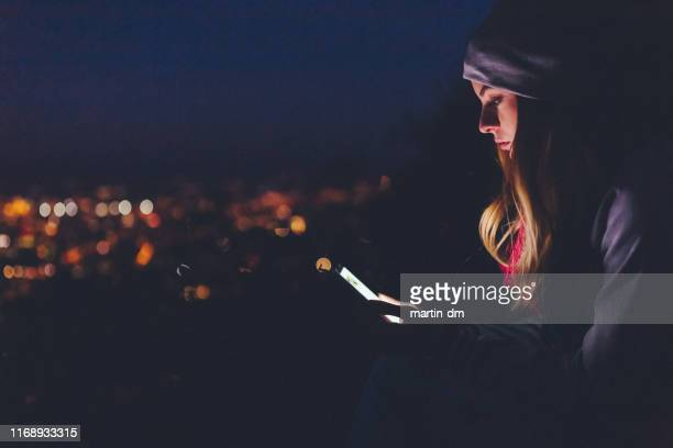 woman in the city texting by night - surfing the net stock pictures, royalty-free photos & images