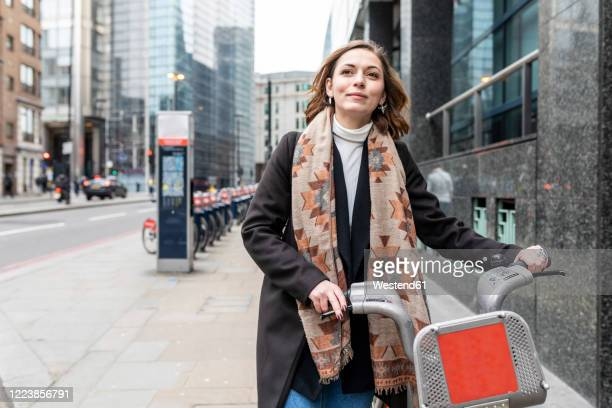 woman in the city using rental bike, london, uk - looking away stock pictures, royalty-free photos & images