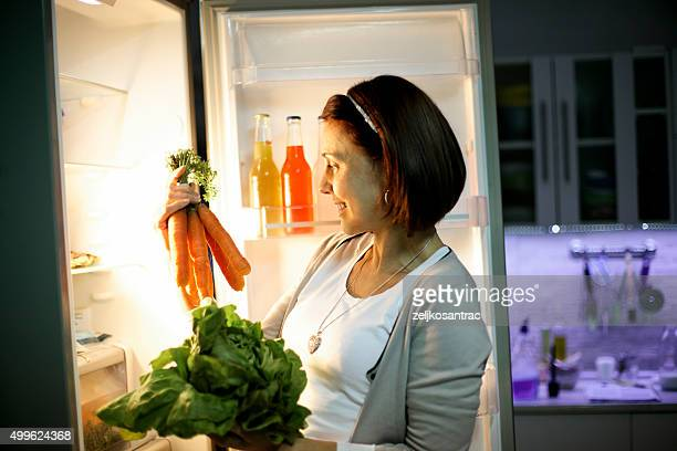 Woman in the dark at open refrigerator
