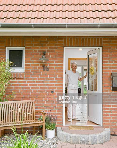 woman in the doorway of a home - doorway stock pictures, royalty-free photos & images