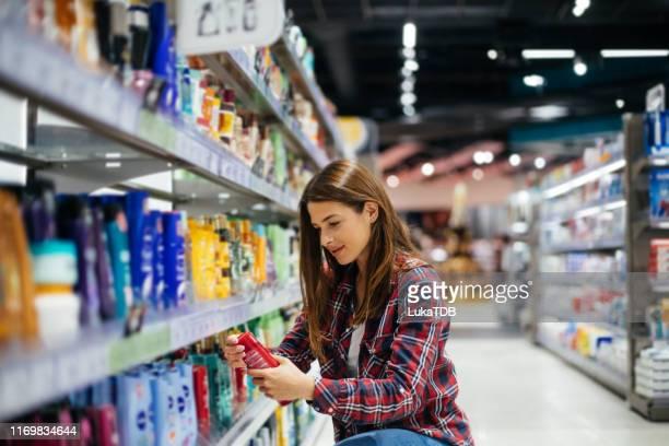 a woman in the drugstore isle - convenienza foto e immagini stock