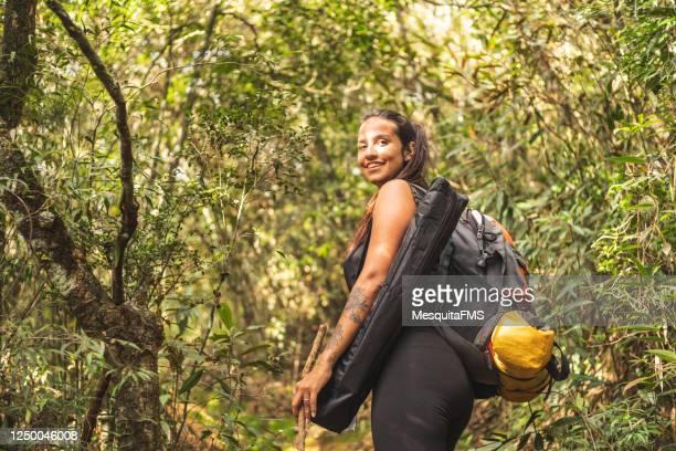mujer en el bosque mirando hacia atrás - turismo ecológico fotografías e imágenes de stock