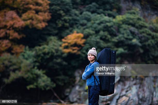 Woman in the forest with rock climbing equipment