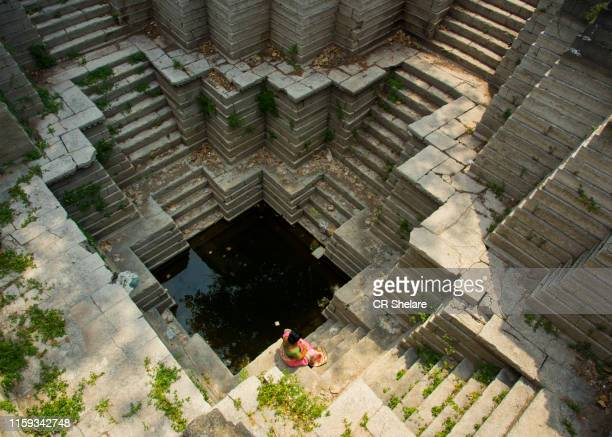 woman in the geometric giant step well, maharashtra, india. - stepwell stock pictures, royalty-free photos & images