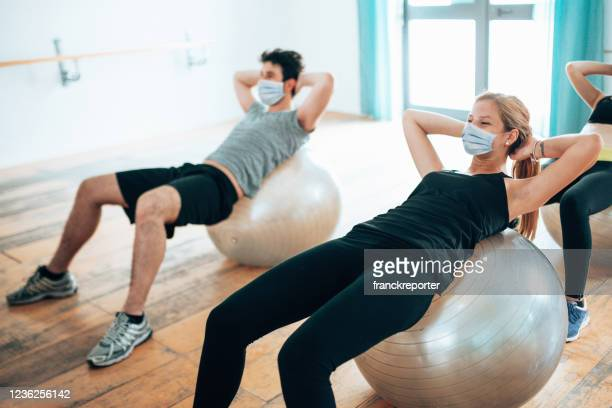 woman in the gym during the covid19 doing abs - gym stock pictures, royalty-free photos & images
