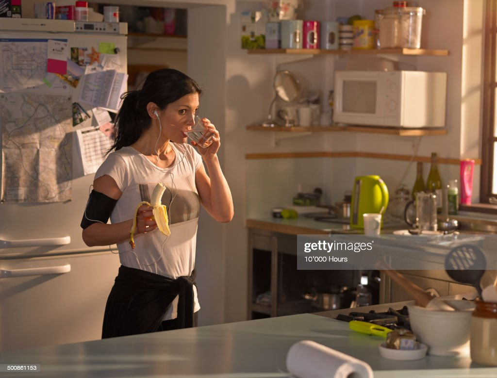 Woman in the kitchen preparing for run : Stock Photo