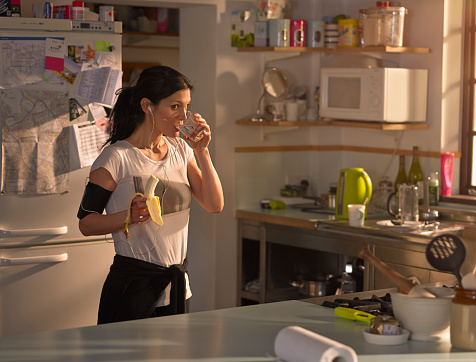 Woman in the kitchen preparing for run - gettyimageskorea