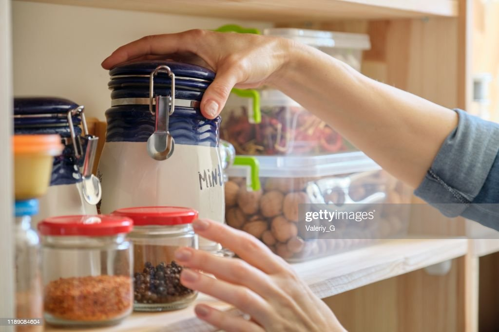 Woman in the kitchen with can of dry mint, food storage, pantry : Stock Photo