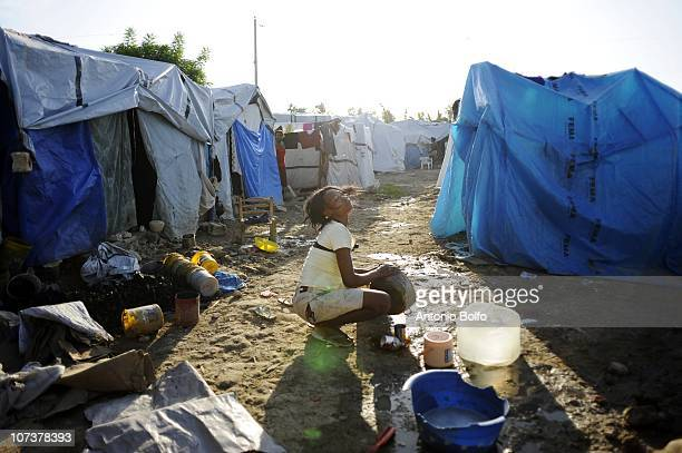 A woman in the Mariani tent camp bathes November 1 2010 in Port au Prince Haiti The plethora of streams and rivers throughout the city make the risk...