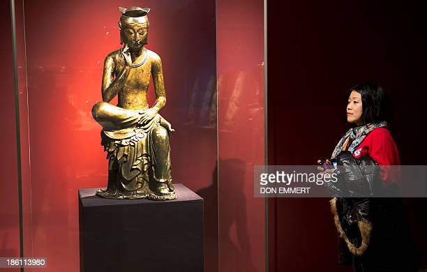 A woman in the Metropolitan Museum of Art looks at the Bodhisattva in a pensive pose which is part of the Silla Exhibit October 28 2013 at the...