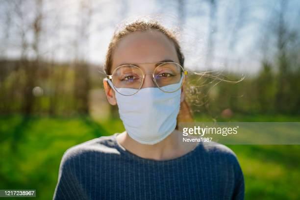 vrouw in de aard die beschermend gezichtsmasker draagt - bril brillen en lenzen stockfoto's en -beelden