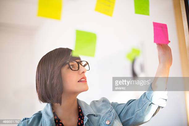 Woman in the office looking at posit notes