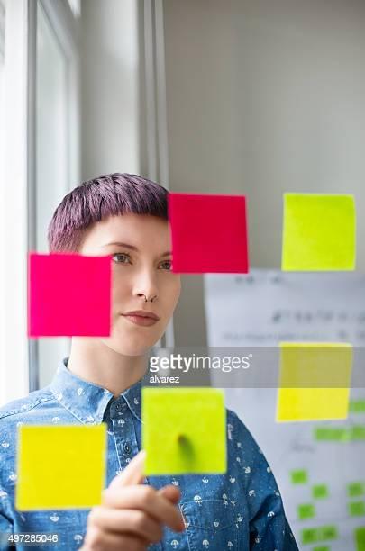Frau im Büro, die im posit Notizen