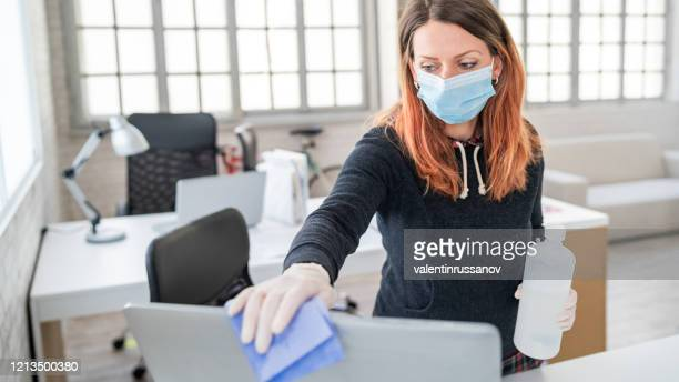 woman in the office using disinfectant  for sanitizing monitor surface during covid-19 pandemic - protective workwear stock pictures, royalty-free photos & images