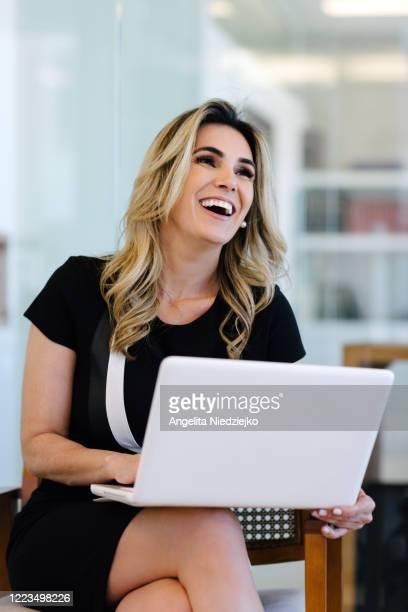 woman in the office with lappot on her lap - finanças e economia - fotografias e filmes do acervo