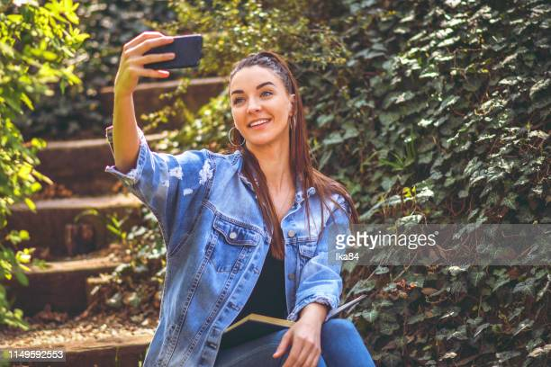 a woman in the park taking a selfie - phone cover stock pictures, royalty-free photos & images