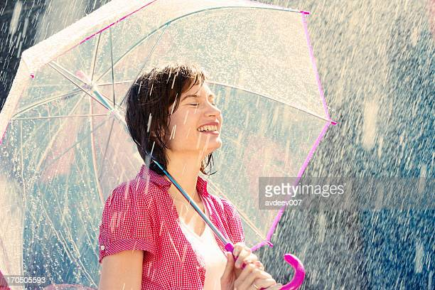 Woman in the rain with a pink and clear umbrella