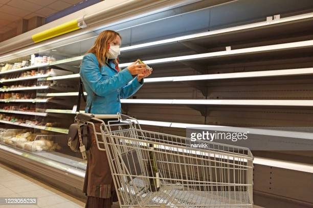 woman in the shop at empty shelves - panic buying stock pictures, royalty-free photos & images