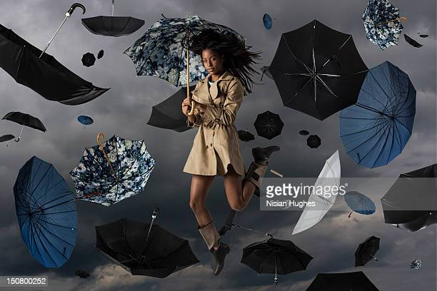 Woman in the sky with umbrellas raining