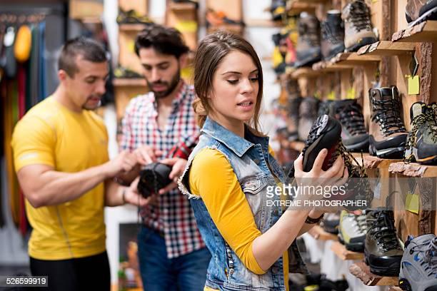 Femme dans la boutique holding chaussures de randonnée