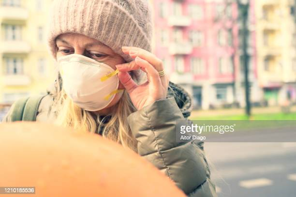 woman in the street putting a protection mask on. berlin, germany. - 1918 flu pandemic stock pictures, royalty-free photos & images