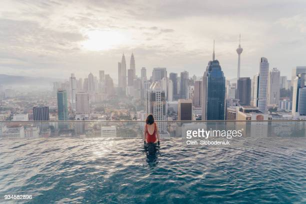 woman in the swimming pool with view of kuala lumpur - kuala lumpur stock pictures, royalty-free photos & images