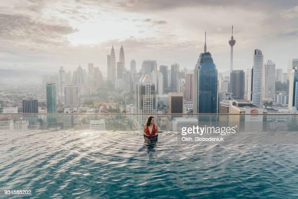 mulher na piscina com vista de kuala lumpur - torres petronas - fotografias e filmes do acervo