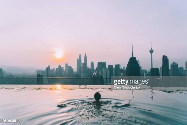 Woman in the swimming pool with view of Kuala Lumpur