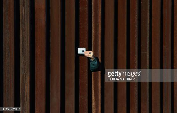 TOPSHOT A woman in the United States takes a picture to Mexico through the border fence as residents of Anapra a neighbourhood on the outskirts of...