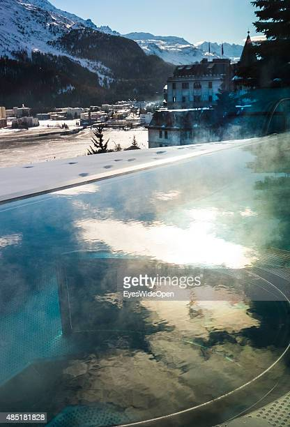 woman in the wellness area and swimming pool interior of the luxury Kulm Hotel with panoramic view on the city and the frozen Lake of St Moritz on...