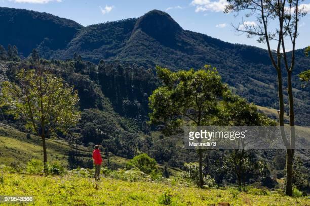 Femme dans les bois à la recherche vers les collines à une journée d'hiver, Gonçalves, Minas Gerais