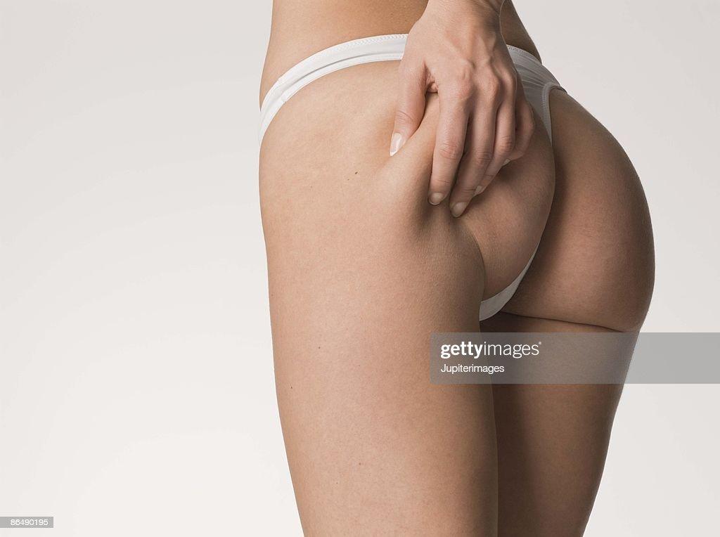 Woman in thong grabbing buttocks : Stock Photo