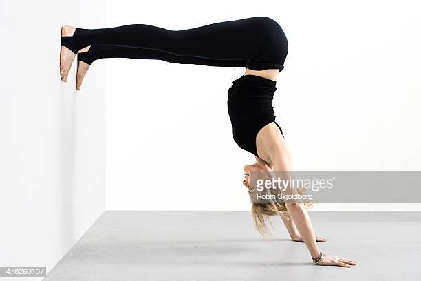 Woman in tights doing handstand against wall
