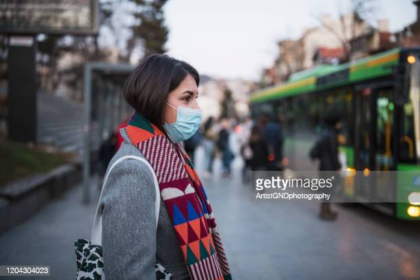 woman in town wearing protective face mask. - protective face mask stock pictures, royalty-free photos & images