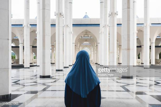 woman in traditional abaya standing in at blue mosque - muslim praying stock pictures, royalty-free photos & images