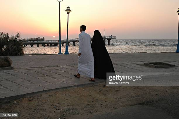 A woman in traditional black abaya walking with her male companion towards the pier on the coast at Jeddah Saudi Arabia 27th November 2005