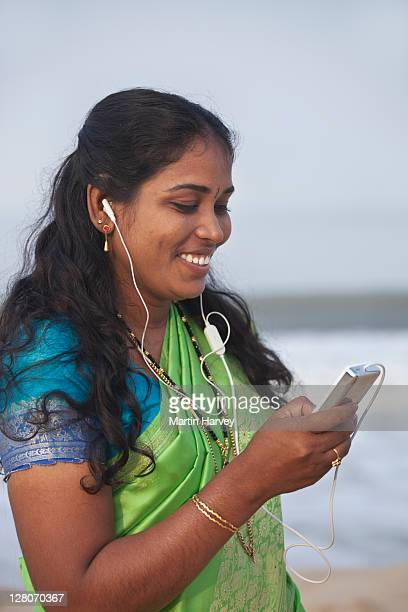 woman (28 years old) in traditional bright green and turquoise sari listening to an mp3 player on marari beach alappuzha, kerala, india - 25 29 years stock pictures, royalty-free photos & images