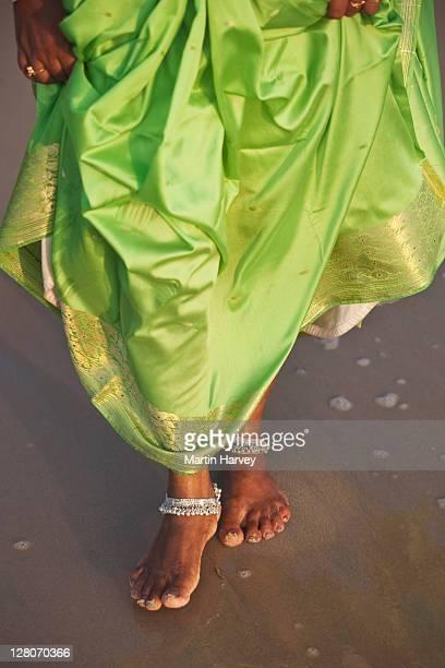 Woman (28 years old) in traditional bright green sari and ankle bracelets walking on Marari beach, Alappuzha, Kerala, India
