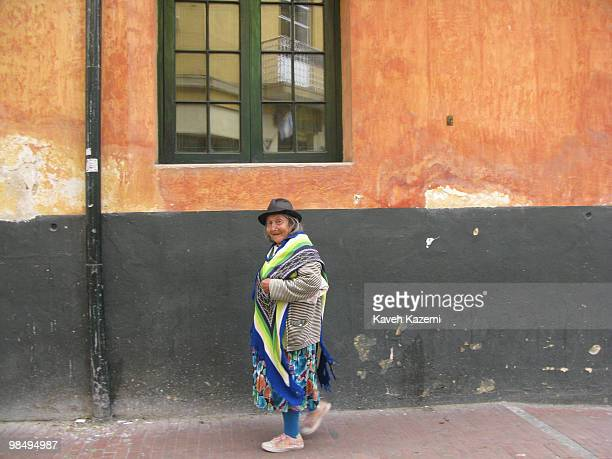 A woman in traditional clothes and a chapeau walks in Candeleria old part of the city Bogota formerly called Santa Fe de Bogota is the capital city...