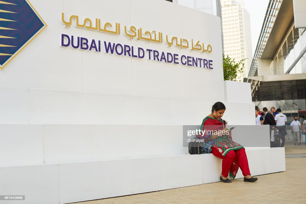 Woman In Traditional Clothes Sitting In Front Of Dubai World