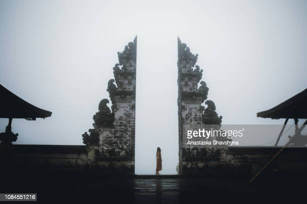 woman in traditional clothes staying in foggy temple on bali - hinduism stock pictures, royalty-free photos & images