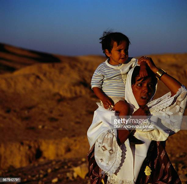 Woman in traditional clothes with a child on her shoulders Matmata Tunisia