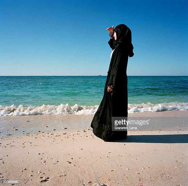 woman in traditional clothing standing on beach - hijab - fotografias e filmes do acervo